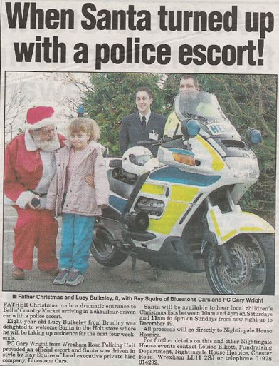 Newspaper cutting of Santa Claus being Chauffeur Driven with police escort.
